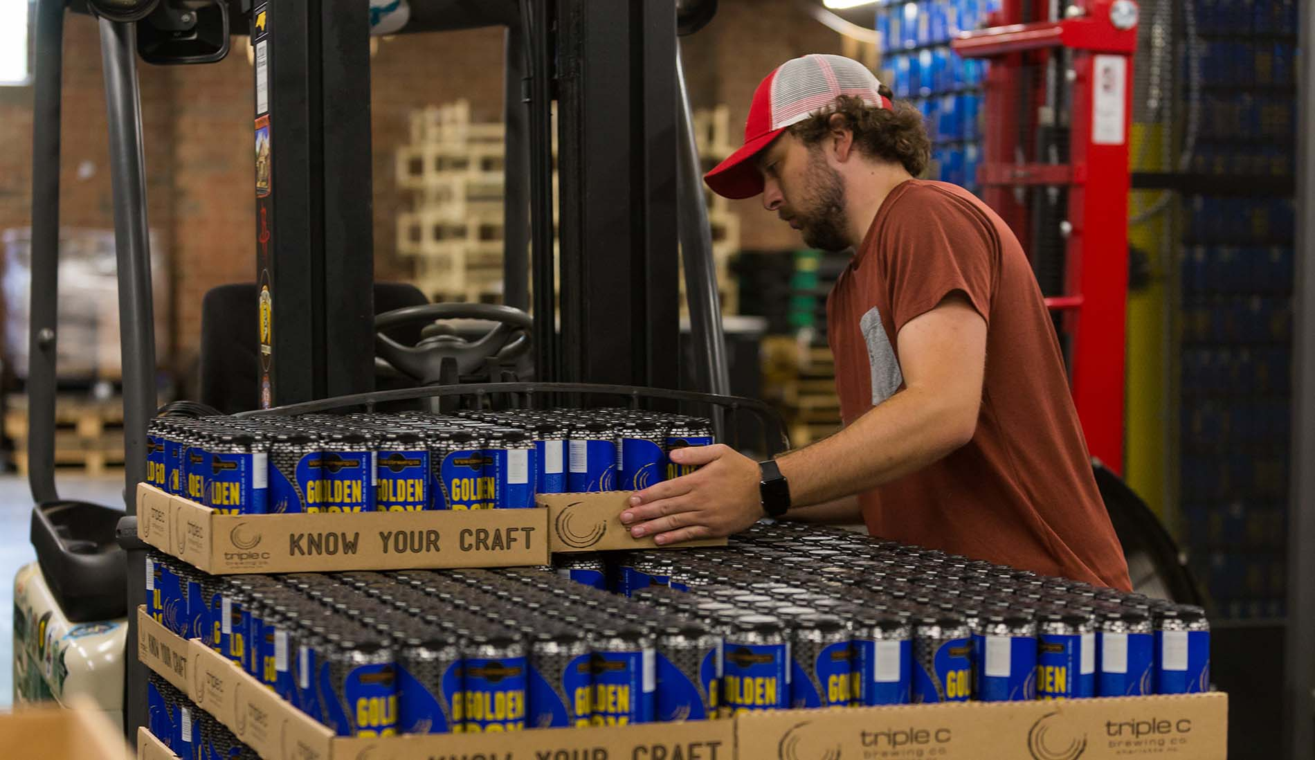 brewery employee stacking beer