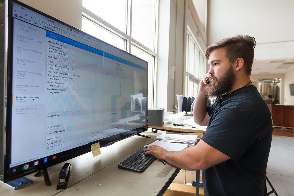 brewery employee standing at computer
