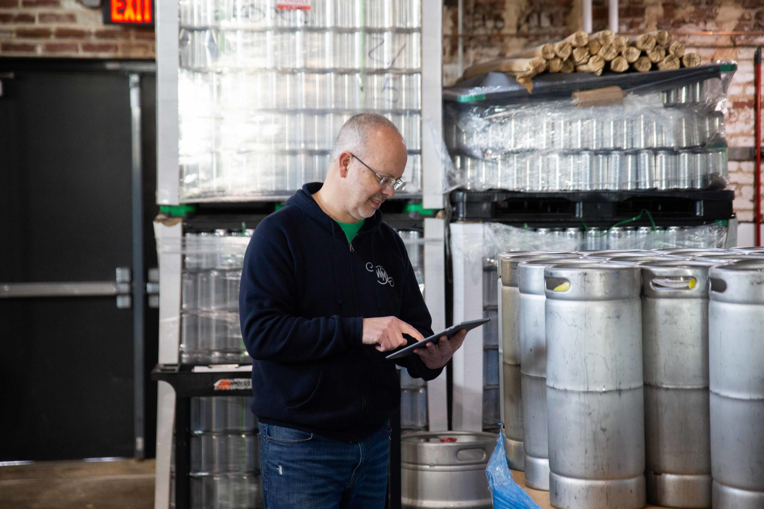 Brewery employee updating inventory with a tablet